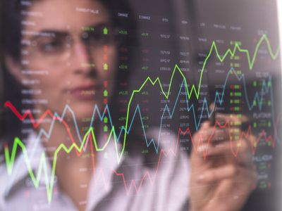 Female analyst viewing financial market data on a screen.