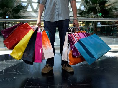 Man holding many shopping bags in mall after a spending spree