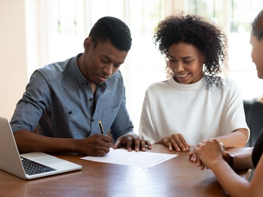 Couple signing paperwork with an insurance agent