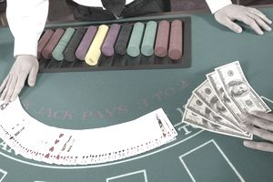 A casino dealer with cards and money on a table