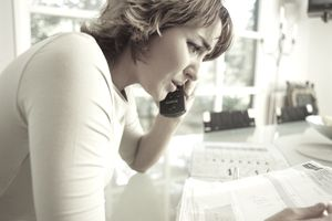 A woman on the phone worried about debt
