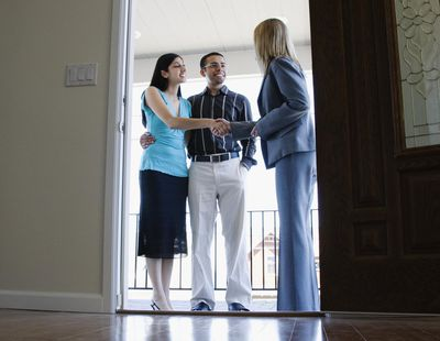 Female realtor greeting young man and woman on front porch