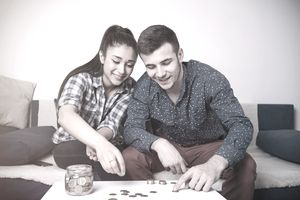 Couple sitting in the couch together counting change from a jar.