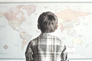 Child looking at a map of the world on the wall