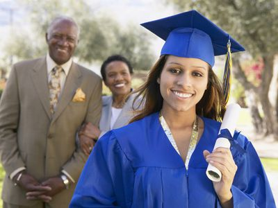 a young woman in her graduation gown and hat with her parents