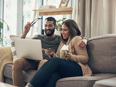 A young couple uses a laptop and credit card on the sofa at home.