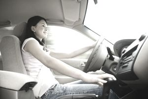 Female teenager behind the wheel of a car
