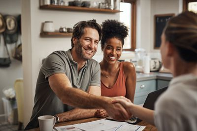 Man seated next to a woman is shaking hands with a financial advisor during a consultation at home