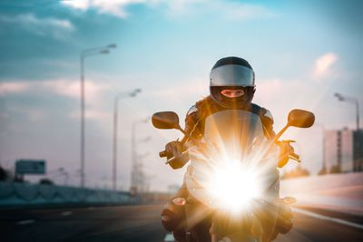 Woman drives on a motorcycle on morning highway