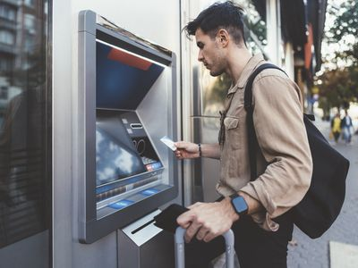 man with suitcase depositing cash into an ATM