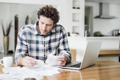Worried man sorting through a stack of receipts and bills at a table holding a laptop.