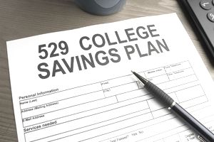 "Form that reads ""529 College Savings Plan"" on a table with a pen."