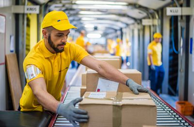 Man processing boxes on conveyor belt in distribution warehouse