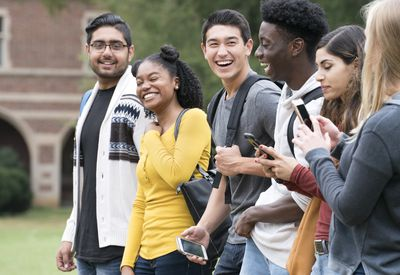 Six college students walk on campus. Four are laughing, one looks at her phone, and one has her back to the camera.