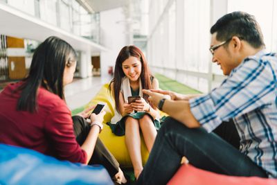Three Asian college students or coworkers using smartphones together.