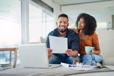 Shot of a happy young couple looking over their finances at home