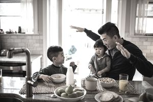 Father and children having breakfast in kitchen