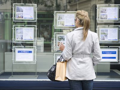 Woman looking at homes for sale ads placed in real estate window