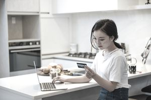 Young woman looking at credit card while sitting in front of laptop