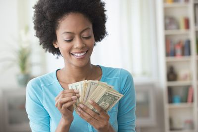 Woman in blue sweater counting cash in her hands