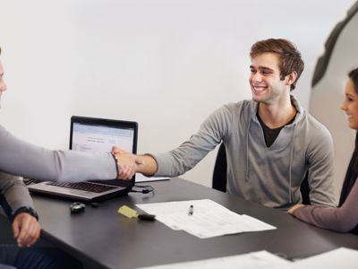 A young car buyer shakes hands across a desk with a salesperson after receiving approval of a co-signed loan