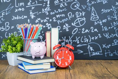 Saving for a college education with a piggy bank, books, pencils, clock and chalkboard.
