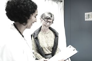 Doctor reviews clipboard with happy female senior patient