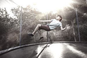 Teeange boy playing with a ball on a trampoline