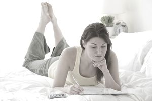 Woman laying on a bed using a calculator as she completes a federal tax return