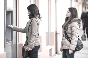 Young woman withdrawing money from an ATM, other woman waiting in line behind her.