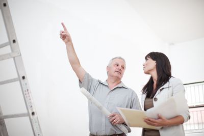 Male and female real estate appraisers talking and pointing upwards holding blueprints next to ladders