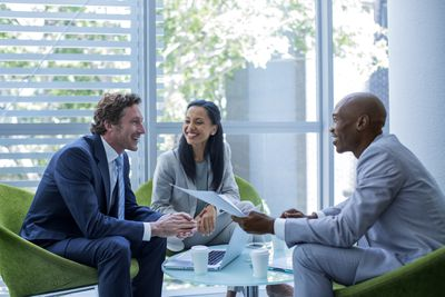 Happy multi-ethnic businesspeople discussing in office