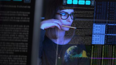 Woman studying stock prices on transparent computer screen