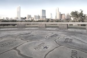 Map of Texas carved into stone patio with Austin skyline in background