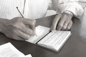 Man sitting at a desk filling out a check in a checkbook