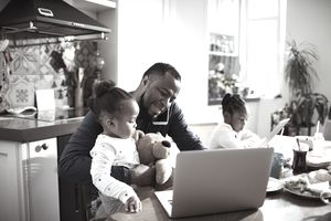 Close up of a young family using a laptop in the morning, while the father is talking on the phone