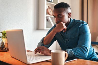 person sitting at wooden desk with computer in front and coffee next to him