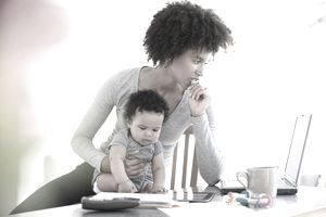 Worried woman holding a baby looking at her finances online.