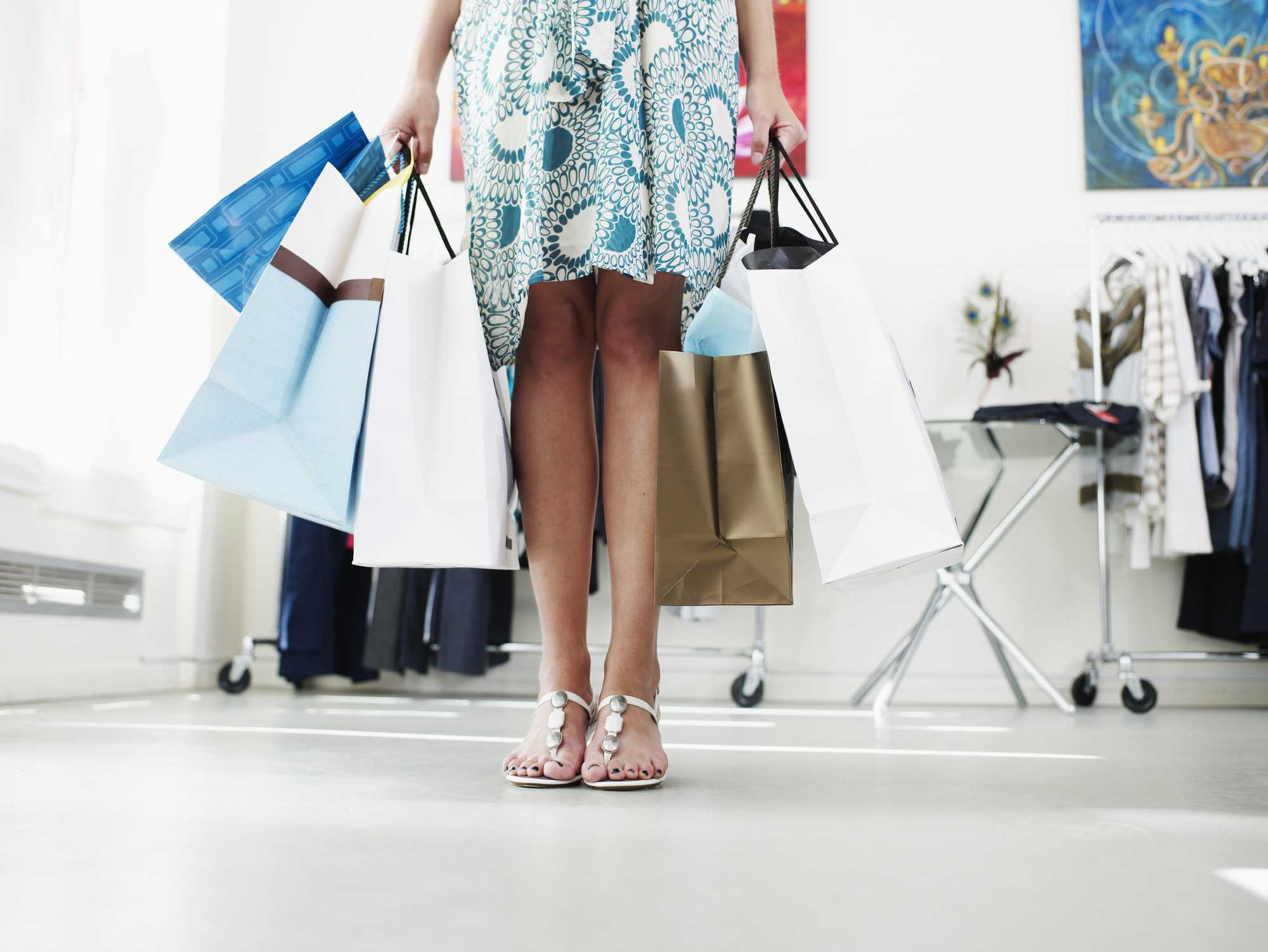 Young woman holding shopping bags in a boutique