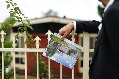 Man in suit looking at house for sale