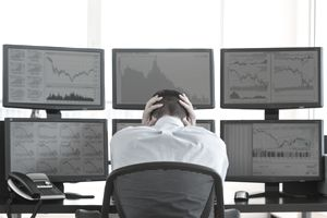 Stock broker sitting at desk in front of computer screens