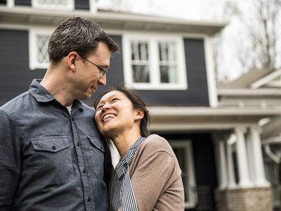 A man and woman hug each other in front of the new home they have just purchased.