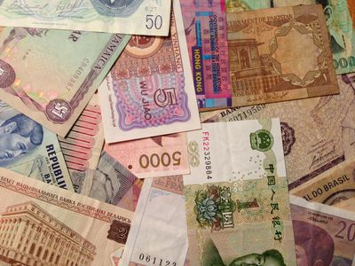 Paper currency from many different countries representing forex trading strategies.