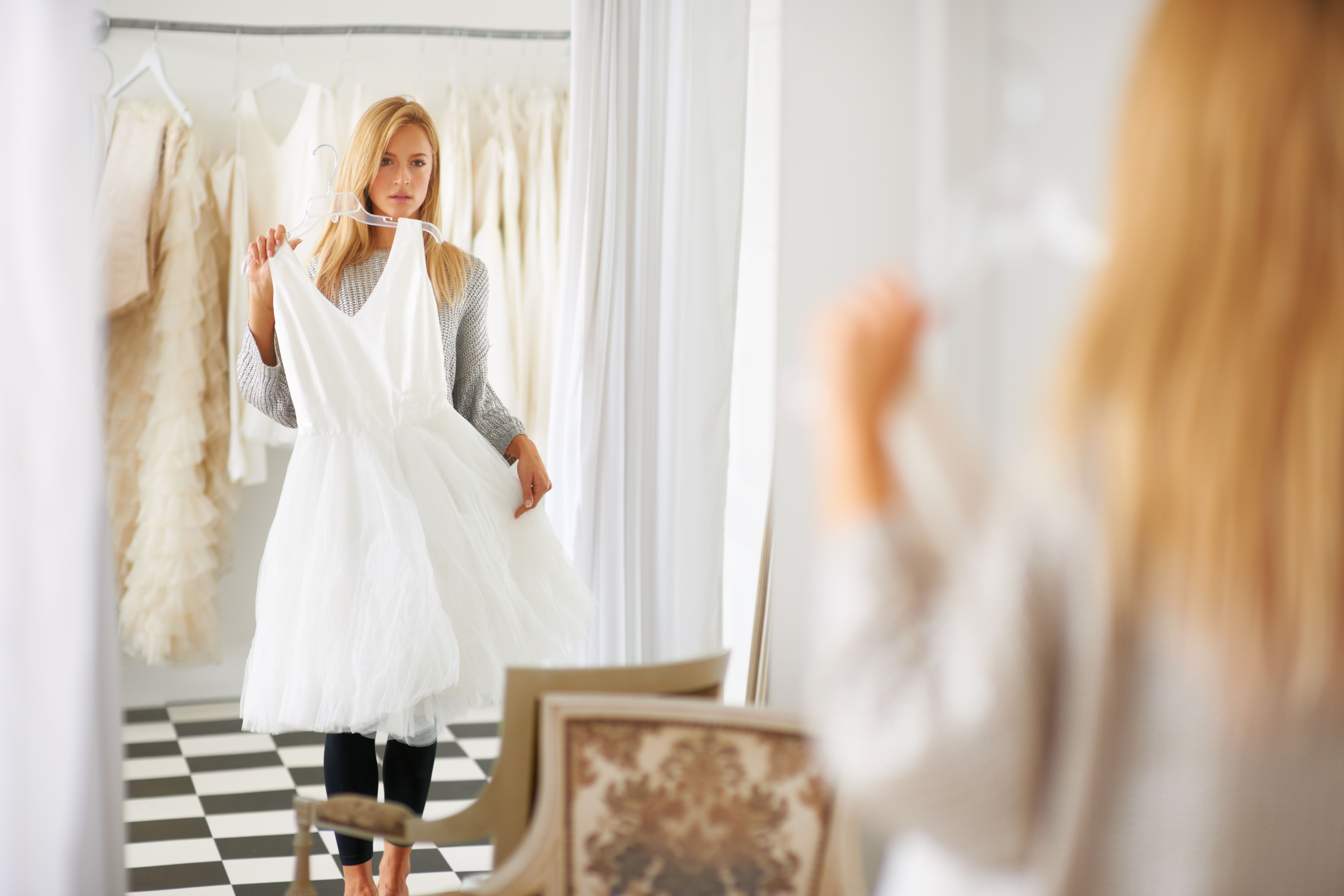 Bride-to-be holding up a possible wedding dress in front of her and looking in a full-length mirror