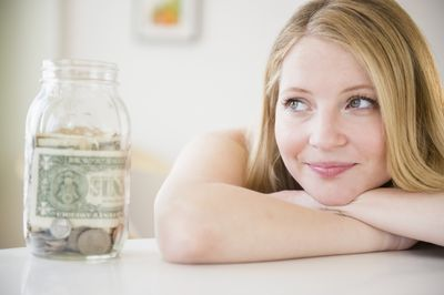 Woman smiling at the start of her savings of coins and bills in a jar