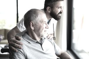 Male caregiver talking to senior man in wheelchair while they look out the window together