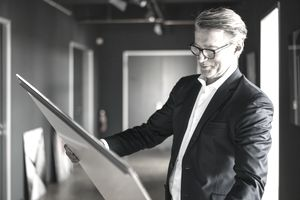 A man in business attire holds a piece of artwork.