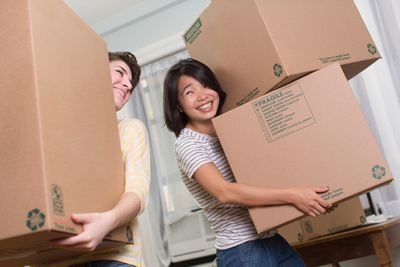 Two young women holding moving boxes