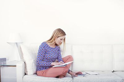A woman using a calculator while sitting on the sofa with papers on her lap