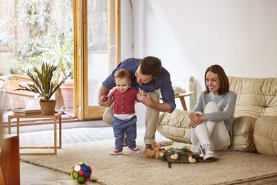 A man helps a baby walk while a woman sits on the floor smiling at them.
